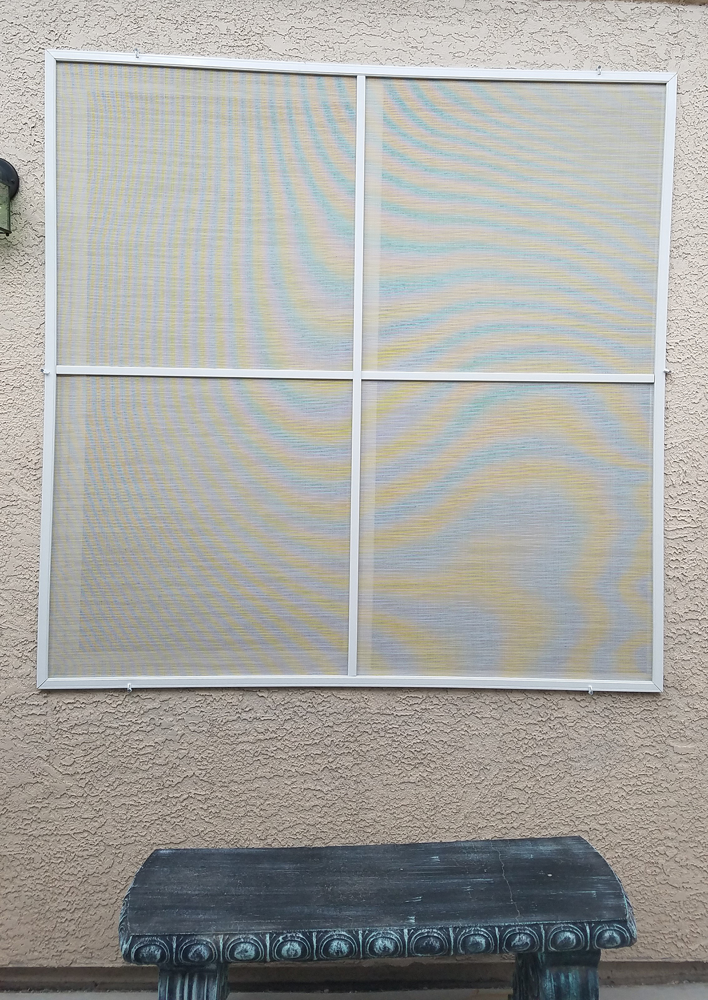 casement window with stucco solar screen and white frames