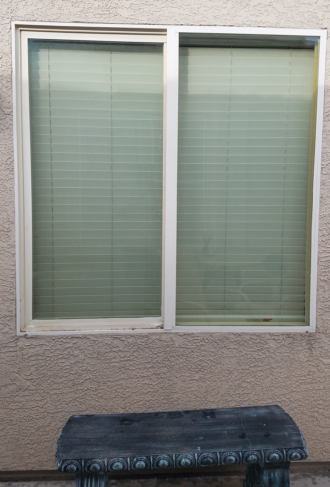 casement window before stucco solar screen and white frames