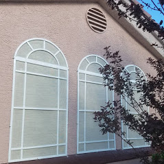 Arched white solar screens with decorative trim