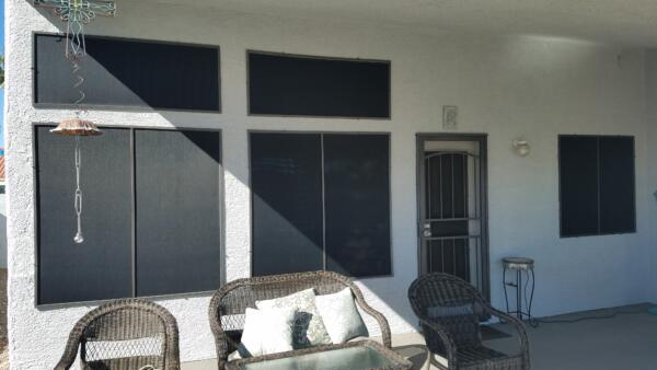 Covered patio with a door, two fixed windows over two slider windows. Screen door and kitchen window