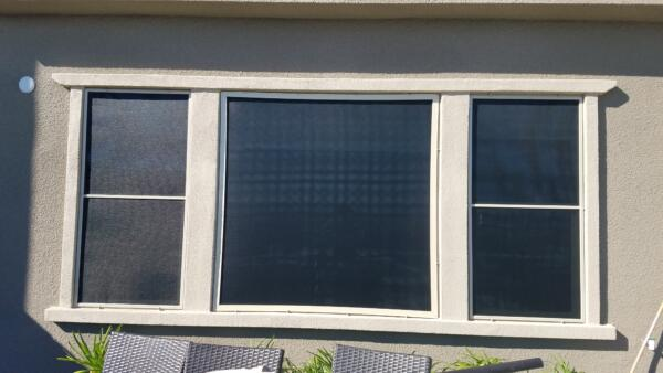 Black sunscreens on picture window flanked by double hung windows on each side