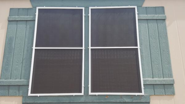Two windows, side by side with sun screens and shutters